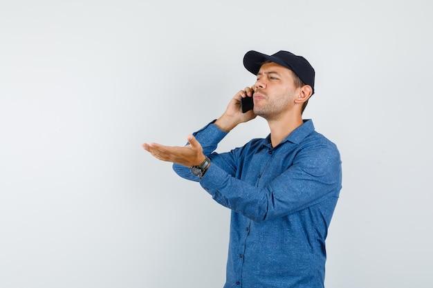 青いシャツ、キャップ、混乱しているように見える、正面図で携帯電話で話している若い男。