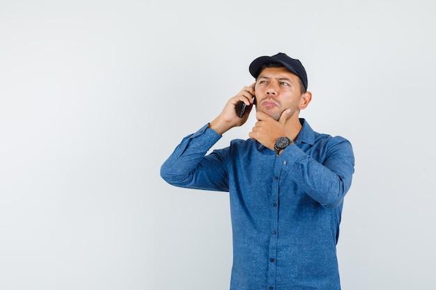 青いシャツ、帽子、物思いにふける携帯電話で話している若い男。正面図。