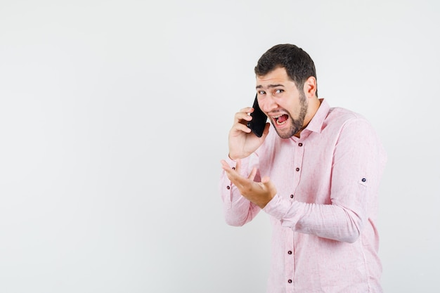 Молодой человек разговаривает по мобильному телефону в розовой рубашке и выглядит сердитым