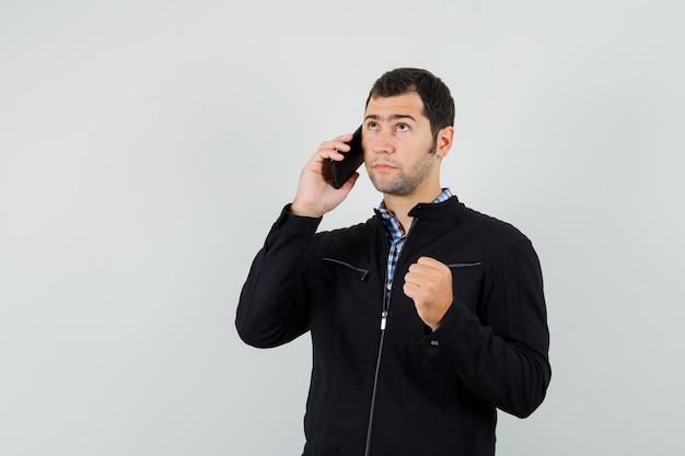 Молодой человек разговаривает по мобильному телефону в рубашке, куртке и задумчиво, вид спереди.