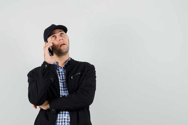 Молодой человек разговаривает по мобильному телефону в рубашке, куртке, кепке и задумчиво смотрит, вид спереди.