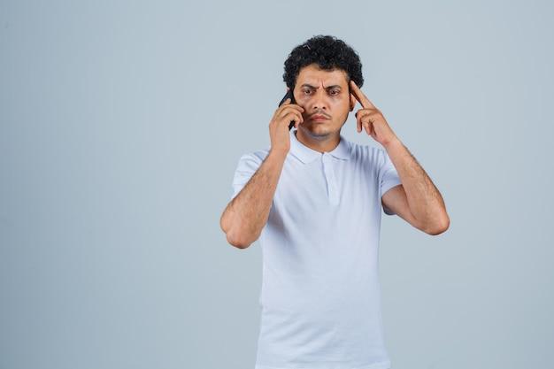 흰색 티셔츠를 입고 휴대폰으로 통화하고 건망증을 보이는 젊은 남자. 전면보기.