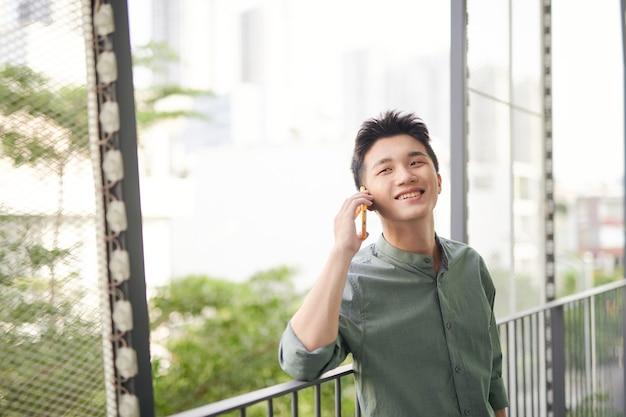 Молодой человек разговаривает по мобильному телефону в саду на крыше