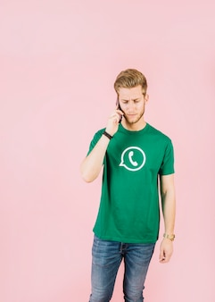 Young man talking on mobile phone over pink background