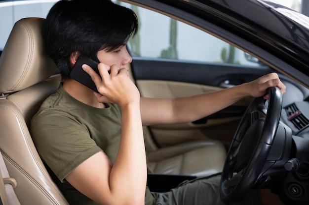 Молодой человек разговаривает по мобильному телефону во время вождения автомобиля.