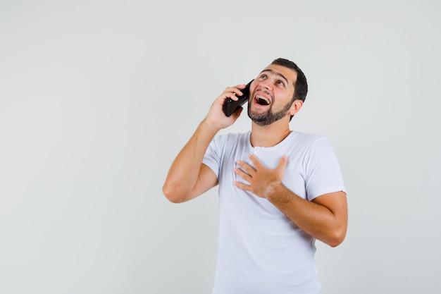 白いtシャツを着て電話で話し、恥ずかしそうに見える若い男、正面図。テキスト用のスペース