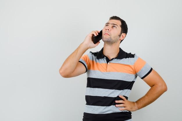 T- 셔츠를보고 사려 깊은 찾고있는 동안 전화 통화하는 젊은 남자. 전면보기.