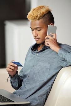 새 신용 카드에 문제가 있을 때 은행 관리자와 전화 통화를 하는 청년