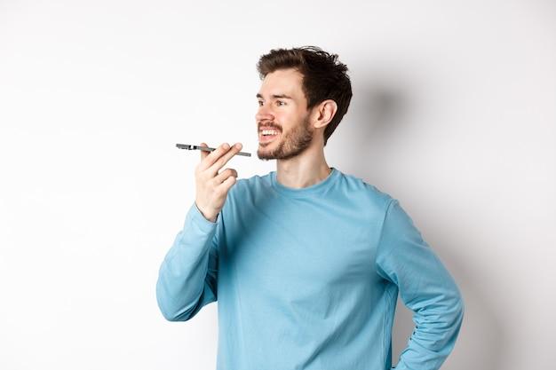 스피커폰에 얘기하거나 응용 프로그램에 음성 녹음을 번역, 흰색 배경에 행복 서 젊은 남자.