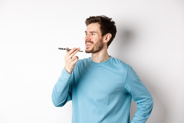 スピーカーフォンで話している、またはアプリケーションで音声録音を翻訳し、白い背景で幸せに立っている若い男