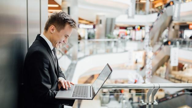 ラップトップでインターネット上で話している若い男、そして笑顔、前向きな顔の感情
