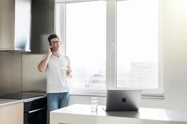 Молодой человек разговаривает по телефону и пьет кофе или чай, стоя на кухне дома