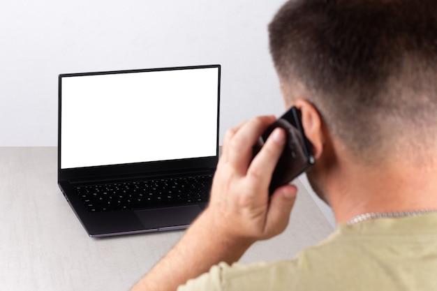 白いモックアップでラップトップの前で電話で話している若い男