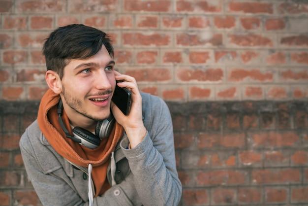 若い男が屋外で電話で話しています。