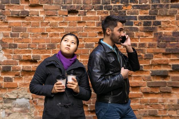 電話で話している若い男、女の子は退屈していて、古いレンガの壁の背景にコーヒーと2つの紙コップを持っています