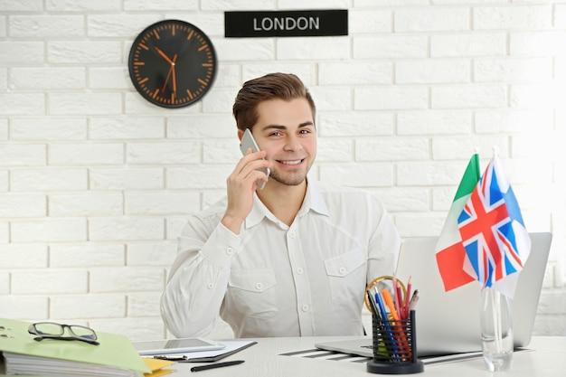 Молодой человек разговаривает по смартфону в офисе туристической компании
