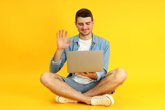 Молодой человек разговаривает по видеосвязи на ноутбуке на желтом фоне.
