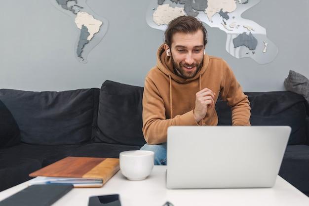 ノートパソコンを使用してビデオ通信で話している若い男