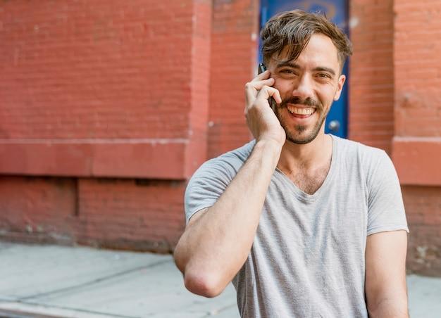 電話で話している若い男
