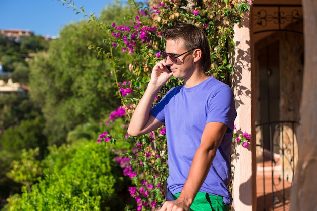 Young man talking on the phone at the balcony