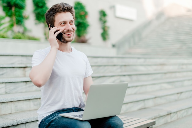 Young man talking on the phone and using laptop for freelance work