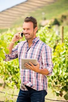 Young man talking on phone at vineyard