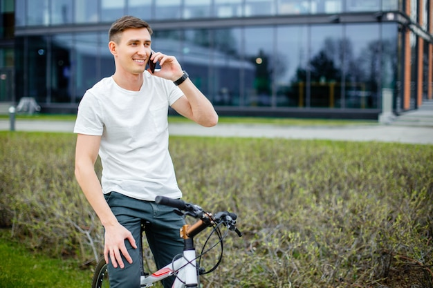 Young man talking on the phone while sitting on a bicycle