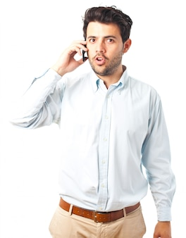 Young man talking on a phone on a white background