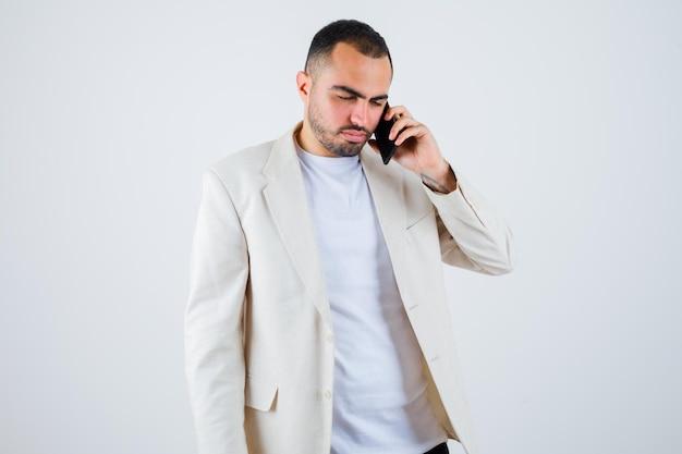 白いtシャツ、ジャケットで電話に話し、真剣に見える若い男。正面図。