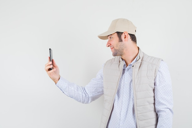 Videocall을 통해 누군가에게 이야기하고 베이지 색 재킷과 모자에 웃고 즐거운 찾고 젊은 남자. 전면보기.