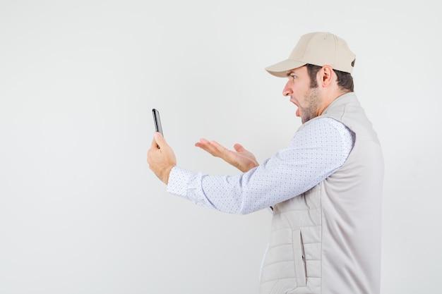 Молодой человек разговаривает с кем-то по видеосвязи в бежевой куртке и кепке и выглядит разъяренным, вид спереди.