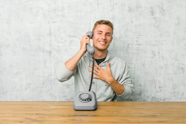 Young man talking on a vintage phone laughs out loudly keeping hand on chest.
