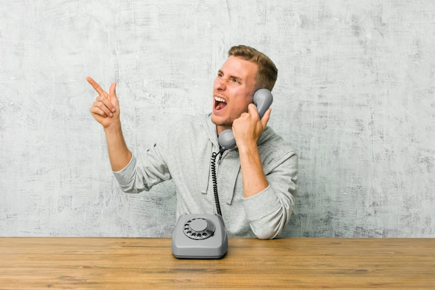 Young man talking on a vintage phone pointing with forefingers to a copy space, expressing excitement and desire.