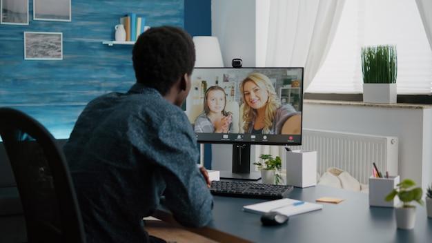Молодой человек разговаривает с друзьями и семьей, используя онлайн-видеозвонок и веб-камеру