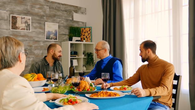 夕食時に60代の父親と話している若い男。おいしい食べ物。