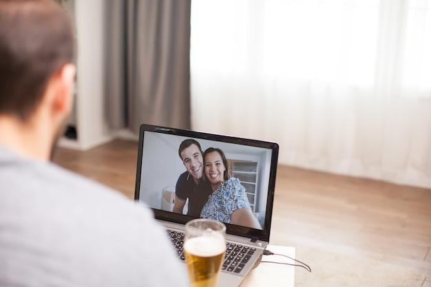 社会的距離の時間にビデオ通話中に彼の友人と話している若い男。