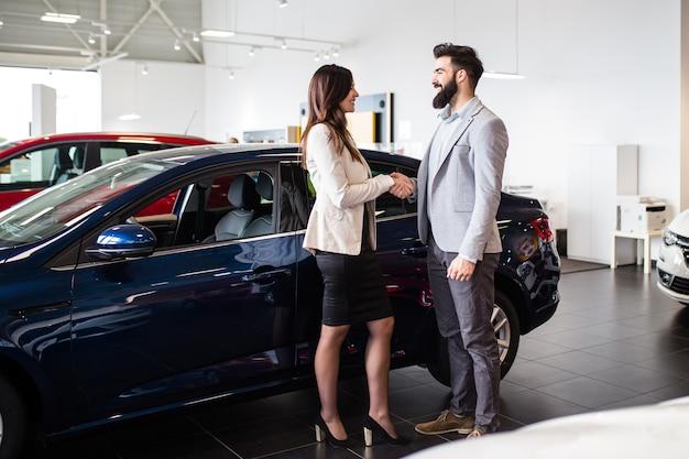 Молодой человек разговаривает с продавцом и выбирает новый автомобиль в автосалоне Premium Фотографии