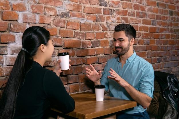 彼らが荒いレンガの壁の背景にあるカフェのテーブルに座っている間、若い男は女の子に何かについて話します