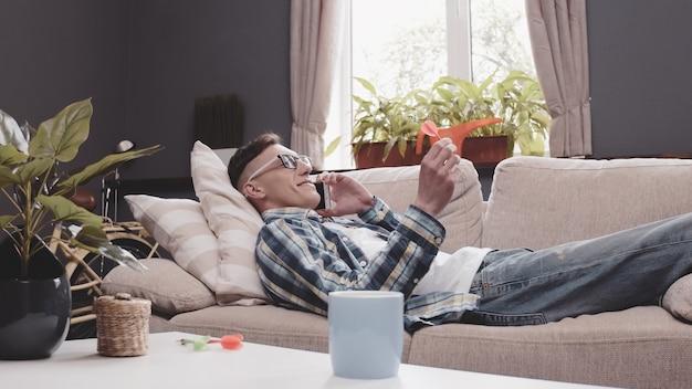 Young man talks mobile phone lying on sofa