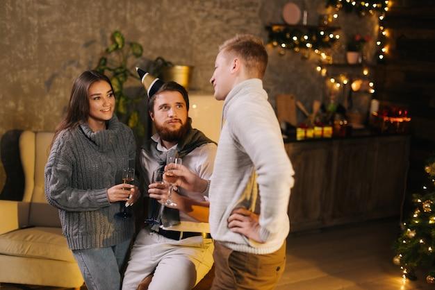若い男は、シャンパンのグラスを手に持ってお祝いに飾られた部屋で大晦日のパーティーを祝うカップルに話します。バックグラウンドでクリスマスツリー。