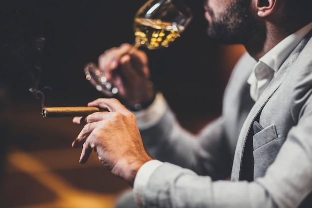 Молодой человек, дегустация белого вина и курение сигары