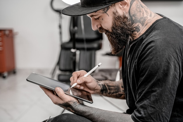 Young man tattoo artist with beard holding pencil and sketch looking positive and happy standing and smiling in workshop place.