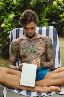 A young man in tattoos wearing headphones listens to music and draws in a notebook.