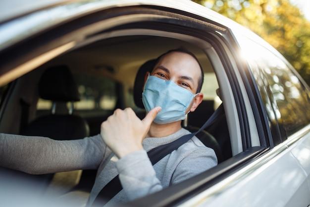젊은 남자 택시 운전사는 차에 멸균 마스크를 쓰고 기호처럼 엄지 손가락을 보여줍니다. 사회적 거리, 새로운 정상, 바이러스 확산 방지 및 치료 개념.