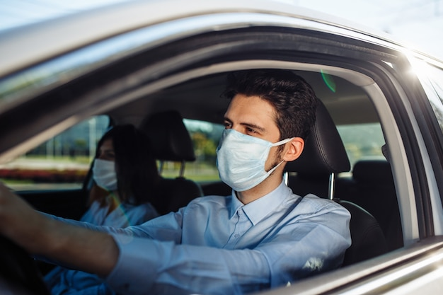 Young man taxi driver wears sterile medical mask in the car. coronavirus pandemic concept.