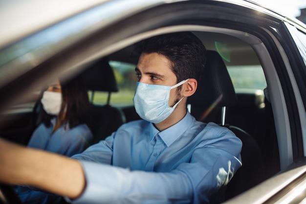 젊은 남자 택시 운전사는 차에 멸균 의료 마스크를 착용합니다. 코로나 바이러스 전염병 개념.