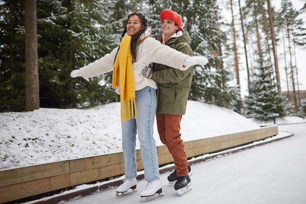 公園のスケートリンクで彼らの時間の間に彼のガールフレンドにスケートを教える若い男