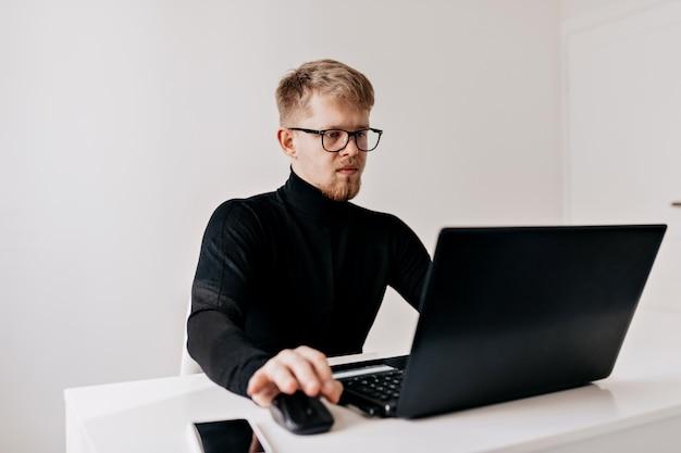 若い男チームリーダー。ラップトップで彼のデスクトップで働いて、彼の明るいオフィスで笑顔で探している自信を持って若い男。