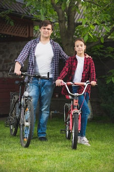 Young man and teenage girl with bicycles having fun at park
