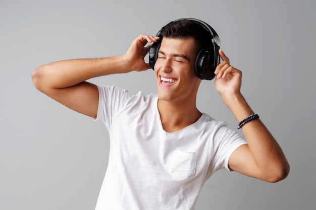 Young man teenager listening to music with his headphones over a grey